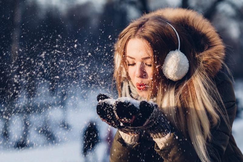Kvinde puster sne og er klar til at skifte til vinterdæk