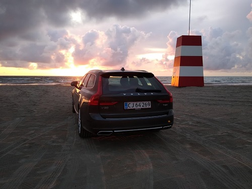 V90 på strand med tårn